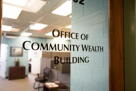 """Glass office door with """"Office of Community Wealth Building"""" lettered"""